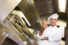 Smiling male cook gesturing thumbs up in kitchen Stock Photos