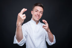 Smiling male cook with his fingers crossed. Wishing you good luck on dark background Stock Photography