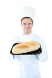 Smiling male cook holding a bread into the camera Royalty Free Stock Image