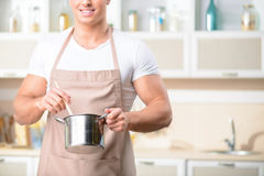 Smiling male cook holding an iron pot Royalty Free Stock Photo