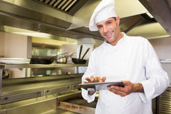 Smiling male cook using digital tablet in kitchen Stock Images
