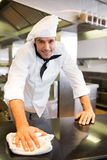 Smiling male cook wiping the counter top in kitchen. Portrait of a smiling male cook wiping the counter top in the kitchen royalty free stock photo