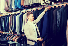 Smiling male customer examining men's suits. Smiling male customer examining suits in men's cloths store Royalty Free Stock Image