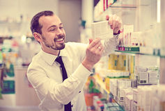 Smiling male customer looking for right medicine Stock Image