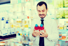 Smiling male customer looking for right medicine Royalty Free Stock Image