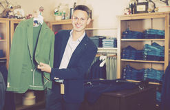 Smiling male customer searching new jacket. In man clothes store Royalty Free Stock Photo