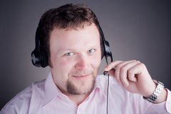 Smiling male customer service operator in headset. Read something from the paper Stock Photos