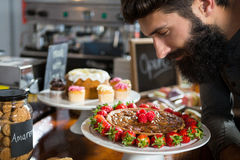 Smiling male customer smelling strawberry pie at counter Stock Photography