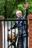Smiling male cyclist waving. Smiling male cyclist in flannel shirt waving hello Royalty Free Stock Images