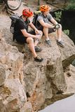 Smiling male cyclists resting with sport bottle of water and apple. On rocky cliff stock photos