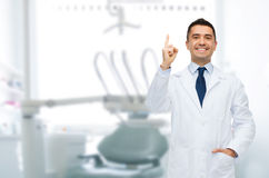 Smiling male dentist pointing finger up Royalty Free Stock Photos