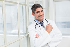 Smiling male doctor with arms crossed in hospital Stock Image