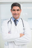 Smiling male doctor with arms crossed in hospital Stock Photos