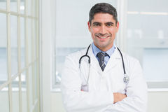 Smiling male doctor with arms crossed in hospital Royalty Free Stock Photography