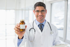 Smiling male doctor with a bottle of pills in hospital Royalty Free Stock Images