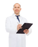 Smiling male doctor with clipboard Stock Photos