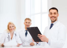 Smiling male doctor with clipboard Stock Photo