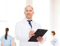 Smiling male doctor with clipboard Royalty Free Stock Photos