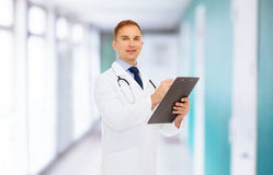 Smiling male doctor with clipboard and stethoscope Royalty Free Stock Photography