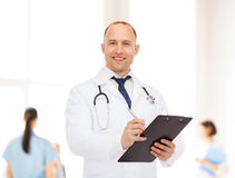 Smiling male doctor with clipboard and stethoscope Stock Photography