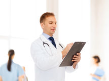 Smiling male doctor with clipboard and stethoscope Royalty Free Stock Photo