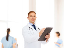 Smiling male doctor with clipboard and stethoscope Royalty Free Stock Image