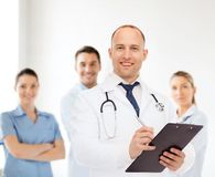 Smiling male doctor with clipboard and stethoscope Stock Photo