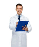 Smiling male doctor with clipboard writing Stock Photo