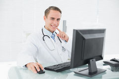 Smiling male doctor with computer at medical office Stock Photo