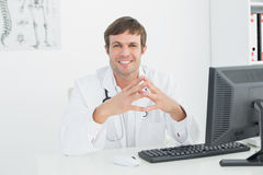 Smiling male doctor with computer at medical office Stock Photos