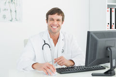 Smiling male doctor with computer at medical office Stock Images