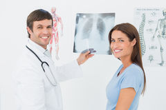 Smiling male doctor explaining lungs xray to female patient. Portrait of a smiling male doctor explaining lungs xray to female patient in the medical office royalty free stock image