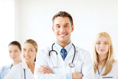 Smiling male doctor in front of medical group Stock Photos