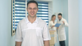 Smiling male doctor in glasses looking at camera while medical staff working on the background. Professional shot in 4K resolution. 098. You can use it e.g. in Stock Photography