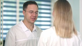 Smiling male doctor in glasses talking to female nurse. Close up shot. Professional shot in 4K resolution. 098. You can use it e.g. in your commercial video stock footage