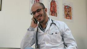 Smiling male doctor having a cheerful phone conversation stock video footage