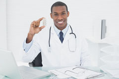 Smiling male doctor holding a prescription bottle Stock Image