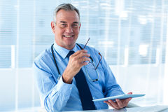 Smiling male doctor holding tablet computer in clinic Stock Photo