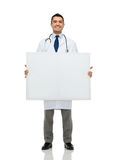 Smiling male doctor holding white blank board Royalty Free Stock Image