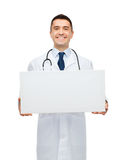 Smiling male doctor holding white blank board Royalty Free Stock Photos