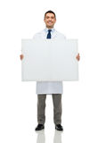 Smiling male doctor holding white blank board Royalty Free Stock Images