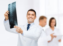 Smiling male doctor holding x-ray at hospital Stock Photos