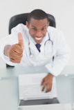 Smiling male doctor with laptop gesturing thumbs up Royalty Free Stock Photo