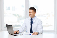 Smiling male doctor with laptop in medical office Royalty Free Stock Image