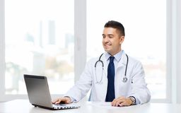 Smiling male doctor with laptop in medical office Stock Photography