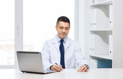 Smiling male doctor with laptop in medical office Stock Photos