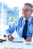 Smiling male doctor looking away in clinic Royalty Free Stock Photos