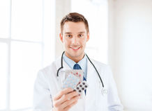 Smiling male doctor with pills in hospital Stock Images