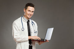 Smiling male doctor posing with laptop Royalty Free Stock Photo