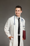Smiling male doctor posing with red laptop Stock Image